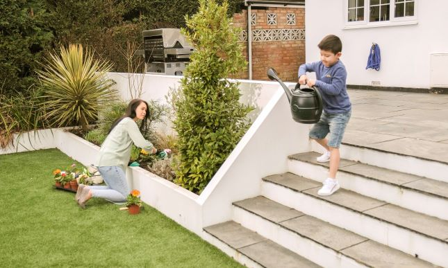 thames water child-carries-a-watering-can-into-the-garden